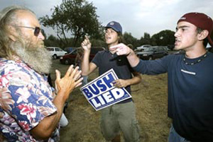 (Paul T. Erickson) Anti-Bush protestors Dan Teimouri, 18, right, and Dash Miller, 19, both of Kennewick exchange heated words with Dewayne Harvill of Burbank who supports Bush. The confrontaion happened in the parking lot of Hood River Park.