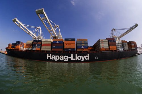 Hapag-Lloyd container ship in the process of being loaded by large container terminal cranes.