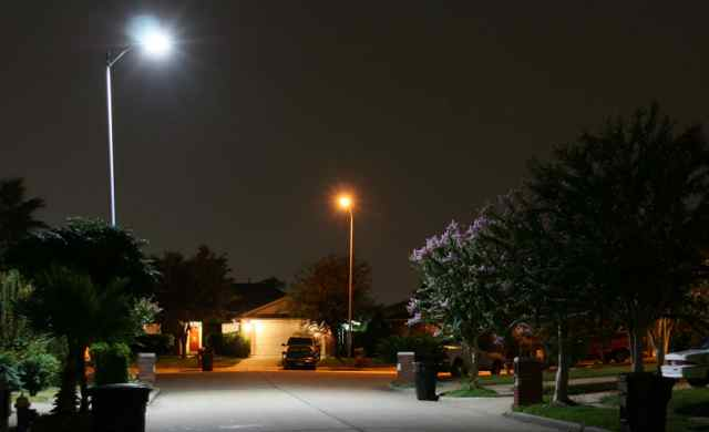 As this streetlight test in Houston shows, LED streetlights (front) emit a whiter light than less-efficient conventional streetlights (back).