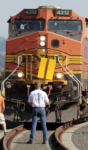A Longshore union member blocks a grain train headed to a Longview terminal in September 2011. The long conflict between the union and operators of grain terminals at Northwest ports officially ended with ratification of a new pact.