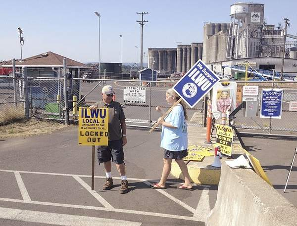 Pete Rasmussen and Michelle Bryant picket the United Grain facility in Vancouver, Wash., which locked out workers from the longshoremen's union last year. Longshoremen and several grain exporters have struck a tentative deal in their labor contract negotiations.
