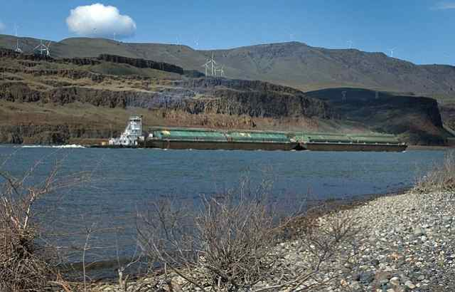 Wind turbines spin lazily above the Columbia River near the John Day Dam as a tugboat pushes barges upriver toward the locks April 19. (Photo by Mark Gibson)
