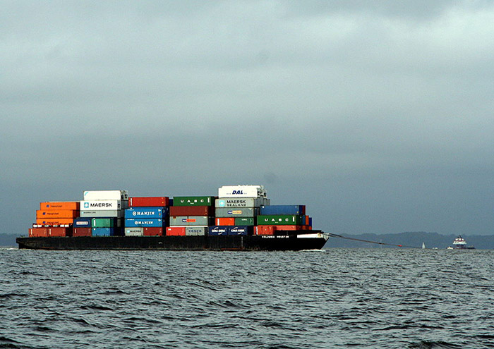 A barge loaded with containers awaiting transfer to ocean-going vessel and shipment to Asia.