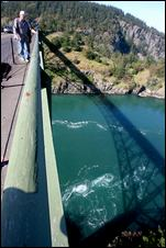 (Scott Eklund) Public utilities and the University of Washington are eyeing tidal power as a source of green energy, a technology that's still in its infancy and raises a lot of questions. Howard McNicol of Seattle checks out the view and the currents on the bridge at Deception Pass.