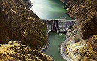 (Idaho Power) Water flows over Hells Canyon Dam, one of three dams in the massive T.E. Roach complex, within the canyon on the Idaho-Oregon border. The other two structures are Oxbow and Brownlee. In the early 1950s, a major controversy over whether to build three privately owned dams or one huge federal structure brought Idaho to the national stage.