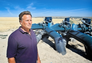 (Dave Wilkins) Randy Brown of the South West Irrigation District stands near a booster station, part of the new West Cassia Pipeline project. The pipeline includes three 24-inch-diameter trunk lines.