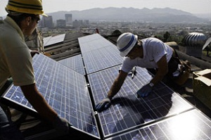 (The Daily Reporter) Solar panels being installed on rooftops.