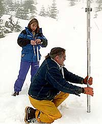 (Steve Ringman) Inspectors record the depth and weight of snow at a Cascades sample site.